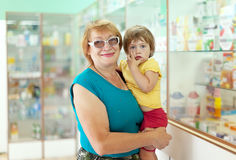 Woman with child chooses drugs at  pharmacy Royalty Free Stock Images