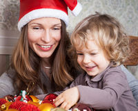 Woman and child in Christmas. Woman and child with Christmas tree decorations Stock Photography