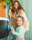 Woman with child cleaning at home Royalty Free Stock Images