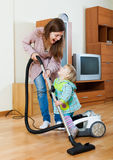 Woman with a child cleaning with a vacuum cleaner Stock Photos