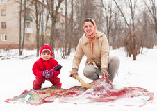 Woman with child cleans rug  in winter day Stock Photography