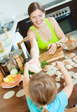 Woman with child cooking fish pelmeni (pelmeni), standing togeth Stock Photography