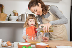 Woman and child cooking pouring oil in bowl Royalty Free Stock Photography