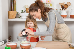 Woman and child cooking serving yogurt. Three years old child with orange apron and women mother with beige, in teamwork, making and cooking a sponge cake at Stock Photography