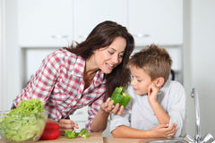 Woman with child cooking vegetables Stock Images
