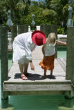 Woman and child on dock. Woman and young girl on a wooden dock pointing and looking down into the water, caucasian/white Stock Photo