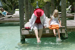 Woman and child on dock. Woman and young girl sitting on a dock at a resort splashing their feet in the water, caucasian/white Royalty Free Stock Photos
