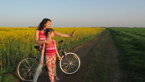 Woman with a child doing selfie in nature. A happy mother with her daughter is photographed in the countryside. Cyclists stock video