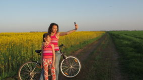 Woman with a child doing selfie in nature. A happy mother with her daughter is photographed in the countryside. Cyclists make self stock footage