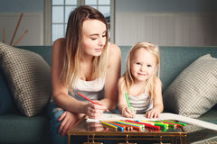 Woman and Child Drawing at Home. Smiling Daughter and Mother Painting royalty free stock photos