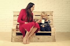 Woman and child drink milk or wine from tea cup. Small boy and girl on bench with cell phone. Kid and mother drinking hot chocolate. Mothers day and new royalty free stock photos