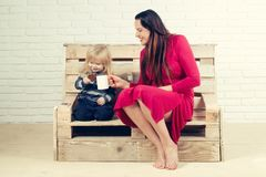 Woman and child drink milk or wine from tea cup. Small boy and girl on bench with cell phone. Kid and mother drinking hot chocolate. Mothers day and new royalty free stock photo