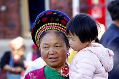 A woman and a child of an ethnic minority of Yunnan with her traditional clothes in the market of Zhoucheng village, Dali, Yunnan, stock image