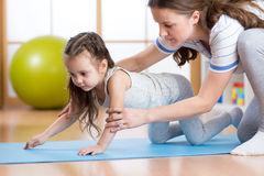 Woman with child exercising in sport hall Royalty Free Stock Image