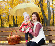 Woman with child girl in autumn city park sit on bench with apples basket and umbrella and having fun, happy family Stock Images