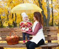 Woman with child girl in autumn city park sit on bench with apples basket and umbrella and having fun, happy family Royalty Free Stock Image