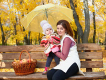 Woman with child girl in autumn city park sit on bench with apples basket and umbrella and having fun, happy family Royalty Free Stock Photography