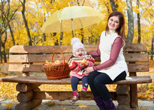 Woman with child girl in autumn city park sit on bench with apples basket and umbrella and having fun, happy family Royalty Free Stock Photos