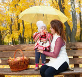 Woman with child girl in autumn city park sit on bench with apples basket and umbrella and having fun, happy family Royalty Free Stock Photo