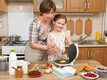 Woman and child girl baking waffles in home kitchen. Raw food and fruits. Healthy food concept. Stock Image