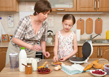 Woman and child girl baking waffles in home kitchen. Raw food and fruits. Healthy food concept. Royalty Free Stock Images