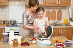 Woman and child girl baking waffles in home kitchen. Raw food and fruits. Healthy food concept. Stock Images