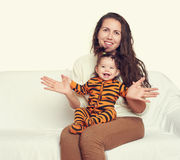 Woman with child girl portrait sitting on sofa and playing Royalty Free Stock Image