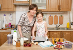 Woman and child girl preparing flour for baking and cookies on a wooden background. Raw food and kitchen utensils. Break an egg, c Stock Photography