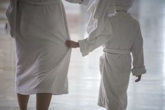 A woman and a child go in white bathrobes stock image