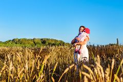 Woman and child in golden ears grain crops field. Woman with child baby in field of golden ears grain crops. Rural life, villagers to harvest. Gathered crops on Stock Image