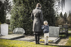 Woman and child at graveyard. Woman with little child at the graveyard looking at the gravestone of daddy. Husband died and now a widower with a little kid Royalty Free Stock Image