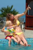 Woman and child have fun in swimming pool Royalty Free Stock Photos