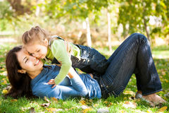 Woman with child having fun in autumn park Stock Photos