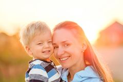 Woman and child having fun outdoors in sunset sunlight Stock Photo