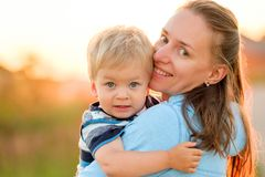 Woman and child having fun outdoors in sunset sunlight Stock Photos