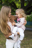 Woman with child having fun in park Stock Photos