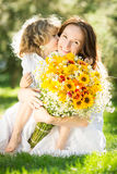 Woman and child holding bouquet of flowers Stock Images