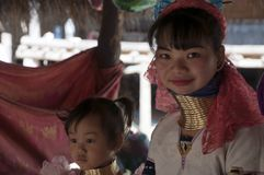 Woman and child from the Karen long neck tribe with brass rings in village tourist market stock image