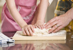 Woman and Child Kneading Dough Stock Photos