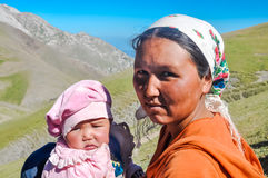 Woman with child in Kyrgyzstan. Arslanbob, Kyrgyzstan - circa July 2011: Native woman with headcloth poses with her small daughter in Arslanbob, Kyrgyzstan Royalty Free Stock Photo