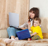 Woman and child with laptops Stock Photography