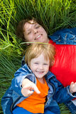 Woman and child lie on green grass Stock Photo