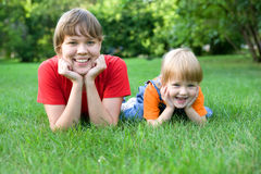 Woman and child lie on green grass Royalty Free Stock Image