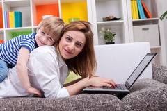 Woman with child lie on sofa Stock Photography