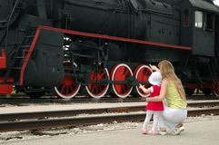Woman with child look at old locomotive Royalty Free Stock Image