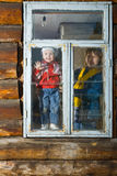 Woman and child look in window. In loghouse Royalty Free Stock Photo