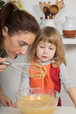 Woman and child looking at whipped cream Royalty Free Stock Image
