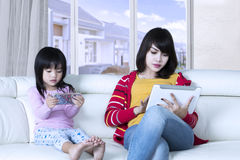 Woman and child looks busy with gadgets Stock Images