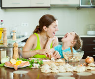 Woman with child making fish dumplings from salmon  at domestic. Smiling women with child making fish dumplings from salmon  at domestic kitchen Stock Photography