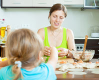 Woman with child making fish dumplings from salmon Royalty Free Stock Photo